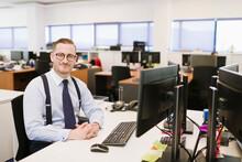 Portrait Of Confident Businessman At Desk In Office