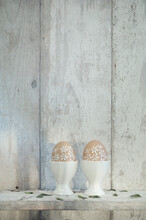 Two Painted Easter Eggs In Egg Cups On Shelf In Front Of Wooden Wall