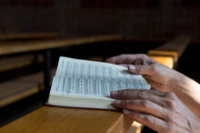 Hands On Hymnbook On Pew