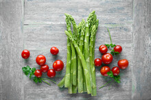 Green Asparagus And Cherry Tomatoes On Wooden Table Seen From Above