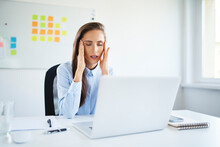 Young Businesswoman Sitting In Office Suffering From Headache