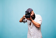 Bearded Young Man In Studio Taking Picture With Instant Camera