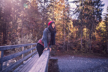 Woman Wearing Red Woolly Hat And Denim Jacket On A Bridge In Autumn