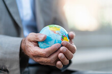 Close-up Of Hands Of Businessman Holding Globe