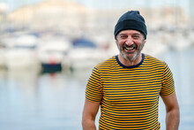 Portrait Of Laughing Mature Man Wearing Cap And Striped T-shirt, Alicante, Spain
