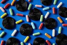 Spiral Wheels Of Licorice Candy With Sugar Coated Licorice On Blue Background