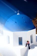 Woman On Top Of A Blue Dome Church Top, Santorini, Greece