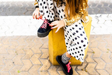 Girl Sitting On Bollard Tying Shoe, Partial View