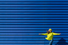Dancing Teenage Girl Listening Music With Headphones In Front Of Blue Background