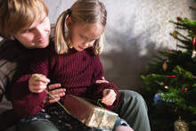 Blonde Girl Sitting On Father's Lap And Opening Christmas Present