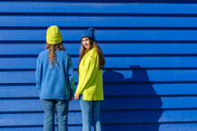 Two Teenage Girls Wearing Matching Clothes Standing In Front Of Blue Background