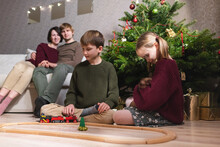 Boy And Girl With Catt, Playing With Toy Train On Wooden Railway Near Christmas Tree And Parents Sitting On The Sofa Behind Their Children