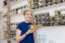 Portrait Of Smiling Woman Holding Jar In Front Of Spice Shelf In Kitchen