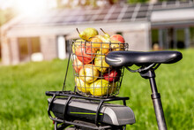 Wire Basket With Apples On Bicycle Rack With House In Background
