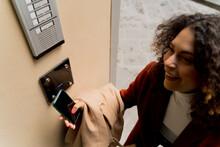 Smiling Woman Opening Door With Smartphone