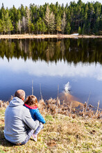 France, Pyrenees, Back View Of Father And Little Daughter Sitting In Front A Lake Looking At View
