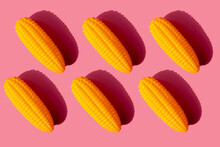 Studio Shot Of Six Plastic Corn Cobs Against Pink Background