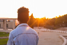 Young Man Wearing Denim Jacket Standing In Park During Sunset
