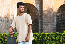Thoughtful Young Man With Skateboard Standing Against Historic Building