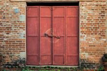An Old Rusty Metal Door Between Exposed Brick Walls