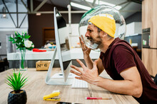 Frustrated Businessman With Fishbowl In Head Screaming While Using Computer In Modern Office
