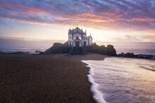 Portugal, Porto District, Vila Nova De Gaia, Long Exposure OfÔøΩPraia De Miramar AndÔøΩCapela Do Senhor Da Pedra At Moody Sunset