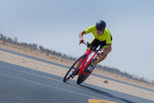 Determined Cyclist Riding Bicycle On Road Against Clear Blue Sky At Desert In Dubai, United Arab Emirates