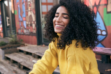 Smiling Young Woman With Eyes Closed Sitting Against Wall In City