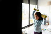 Portrait Of Little Girl Exercising With Dumb Bells At Home