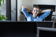 Smiling Businesswoman Sitting With Hands Behind Head On Chair At Office
