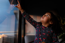 Little Girl Looking Out Of Window In The Evening