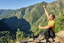 Mid Adult Man Yawning With Hand Raised In Forest On Sunny Day