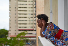 Serious Woman Wearing Colorful Dress Standing On Balcony Looking Out