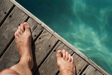 Man's Feet On Floorboard By Swimming Pool During Sunny Day