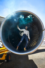 Full Length Portrait Of Smiling Young Woman Holding Distress Flare While Standing Inside Airplane's Turbine At Airport