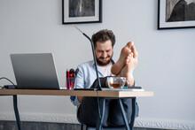 Man Sitting At Desk, Feet Up