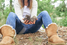Woman Holding Pine Cones While Sitting In Forest