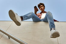 Young Female Hipster Using Smart Phone While Sitting On Retaining Wall Against Blue Sky