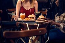 Female Friends Having A Burger In A Pub