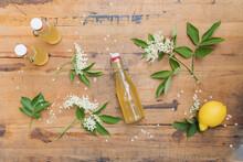 Elderflowers (Sambucus) With Leaves And Elderflower Syrup Bottles On Wooden Table