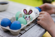 Close-up Of Girl Decorating Easter Egg On Garden Table