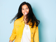 Portrait Of Young Woman With Black Hair Wearing Yellow Denim Jacket, Light Blue Background