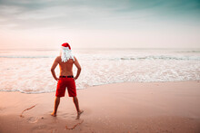 Thailand, Back View Of Man Dressed Up As Santa Claus Standing On The Beach At Sunset Looking At Horizon