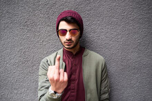 Portrait Of Offensive Man In Mirrored Sunglasses And Purple Hat Showing Fuck At Camera. Isolate On Concrete Textured Background