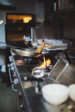 Preparing A Dish At Gas Stove In Restaurant Kitchen