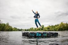 Businessman Jumping On Platform In A Lake