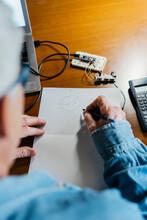 Senior Man Making Diagram On Paper While Repairing Laptop At Home