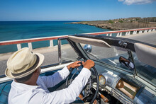 Taxi Driver Driving A Vintage Convertible Car At The Coast On Cuba