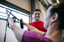 Smiling Fitness Instructor Assisting Woman In Exercising With Straps At Gym