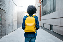Back View Of Young Man With Yellow Backpack On E-Scooter In The City